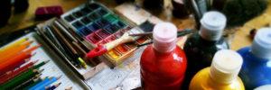 Una taula amb material per pintar: aquarel·les, llapis de colors, pots de pintura...