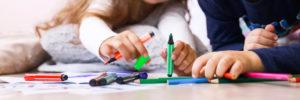 Mans de dos infants que manipulen diversos llapis de colors
